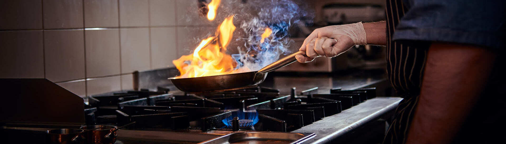 cooker-wearing-gloves-and-apron-frying-flambe-on-a-84NC27C(2)(1)(1)(1)
